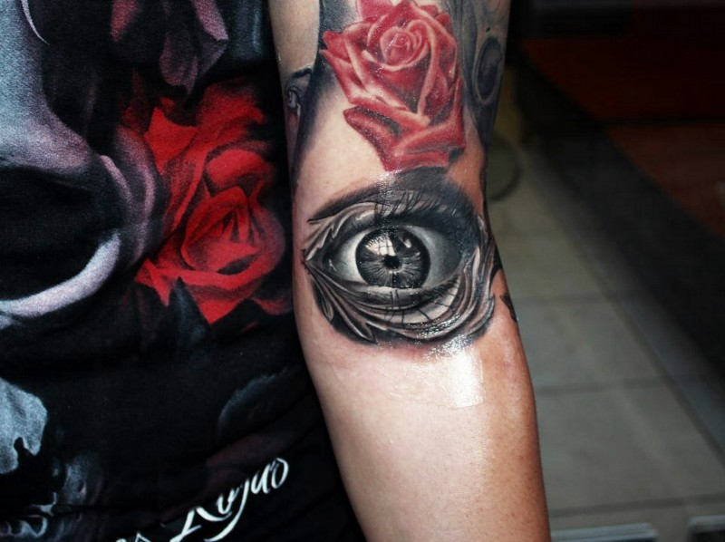3D style black and white arm tattoo of human eye and red rose