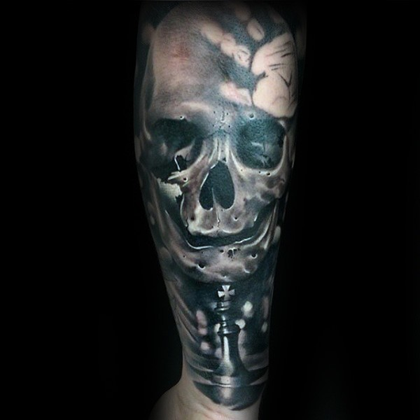 3D style colored forearm tattoo of human skull with chess figures