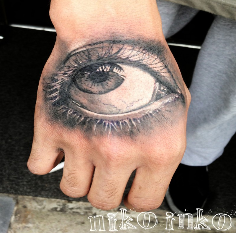 3D style colored hand tattoo of woman eye