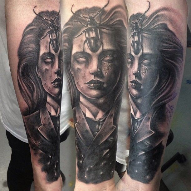 3D style creepy looking black ink forearm tattoo of creepy woman portrait and big bug