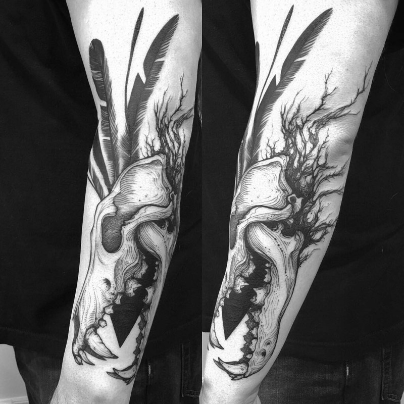 3D style large forearm tattoo of animal skull with black feather