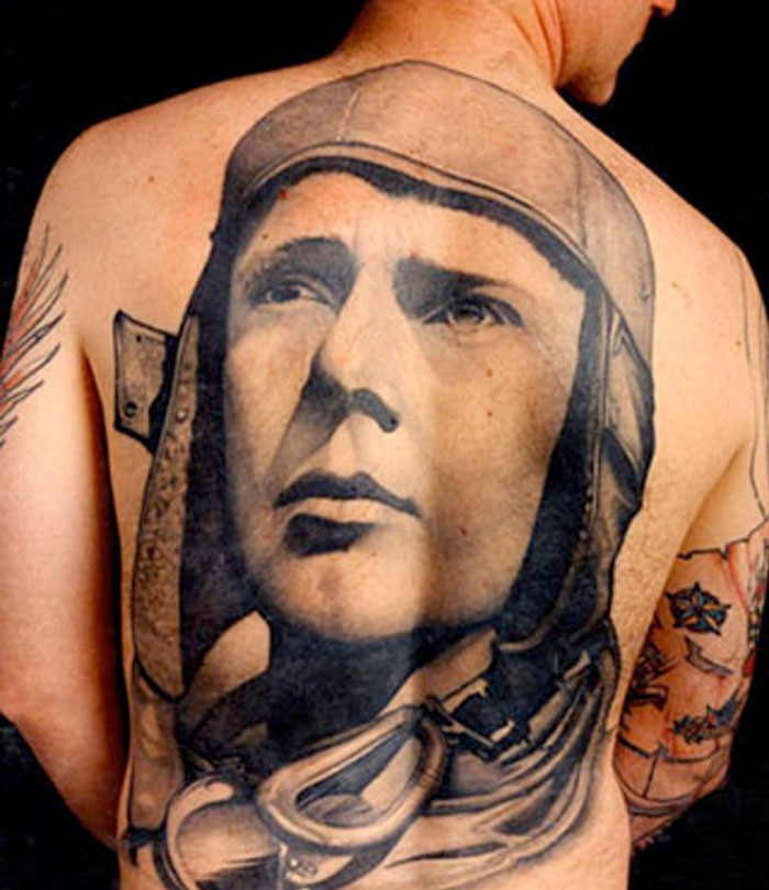Big carelessly painted whole back tattoo of pilot portrait