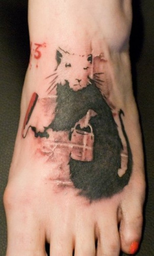 Black-and-white rodent with bucket tattoo on foot