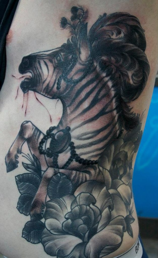 Black-and-white zebra with flowers and fethers tattoo on side