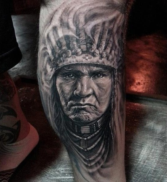 Black and white Indian head tattoo on shin