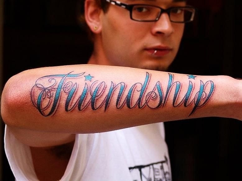 Blue-lettered frendship quote tattoo on arm