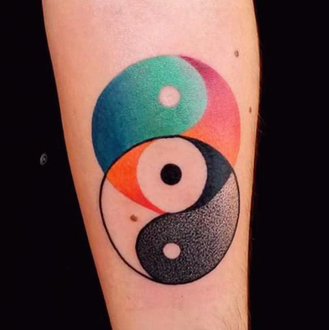 Circle shaped colored upper arm tattoo painted by Mariusz Trubisz of Yin Yang symbols
