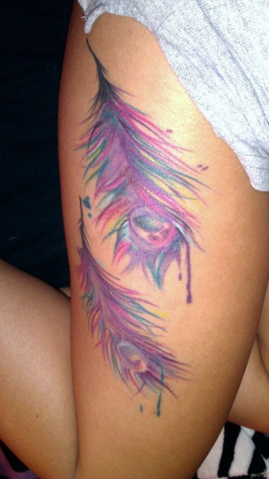 Cool pink-colored peacock feather tattoo on hip