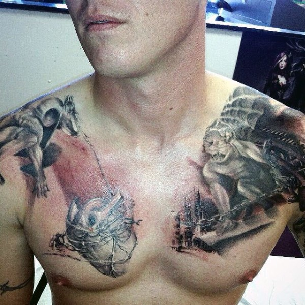 Fantasy style small looking chest tattoo of human heart with gargoyles