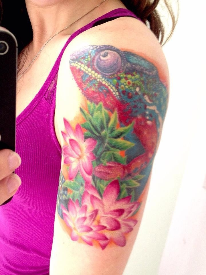 Girly vivid colored chameleon with pink flowers tattoo on arm