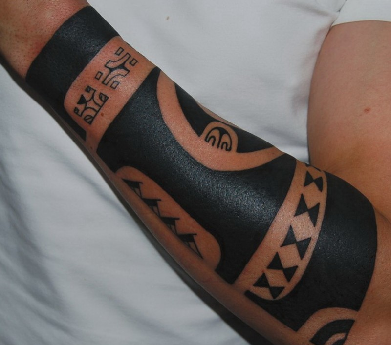 Harsh tribal black-colored tattoo sleeve for men on forearm