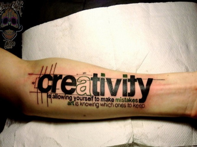 Huge printed black-lettered creativity quote tattoo on arm