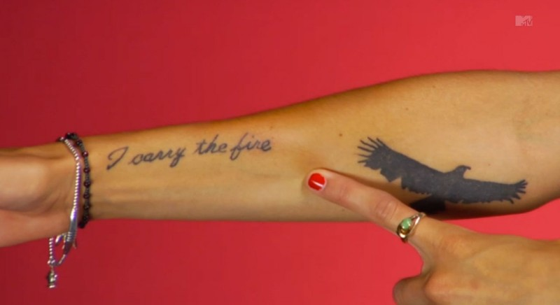 I carry the fire quote with big black bird tattoo on arm