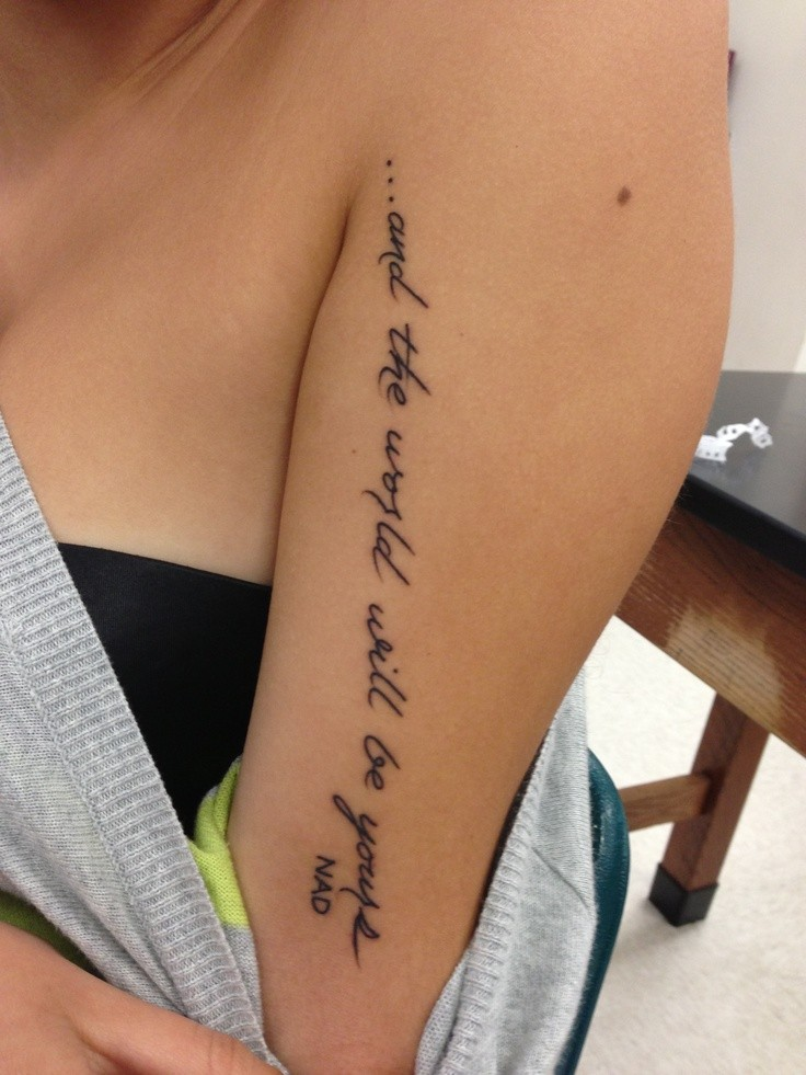 Incomplete black-lettered quote tattoo on arm