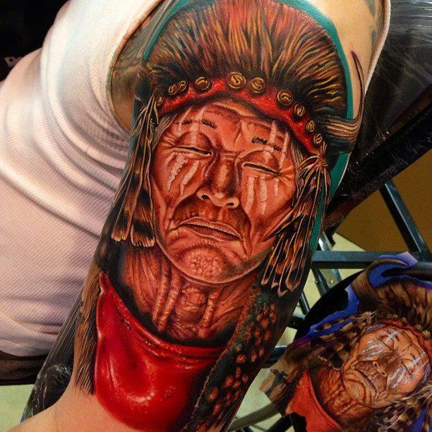 Indian head with closed eyes tattoo on shoulder