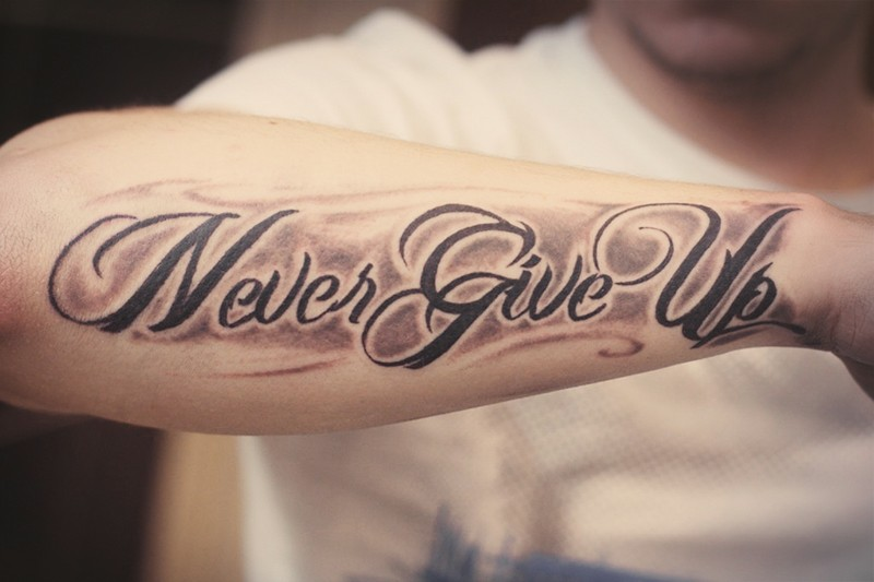 Inspire never give up quote tattoo on arm