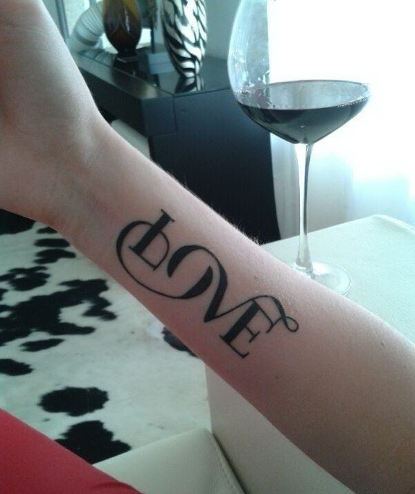 Interesting big-lettered love quote tattoo on arm