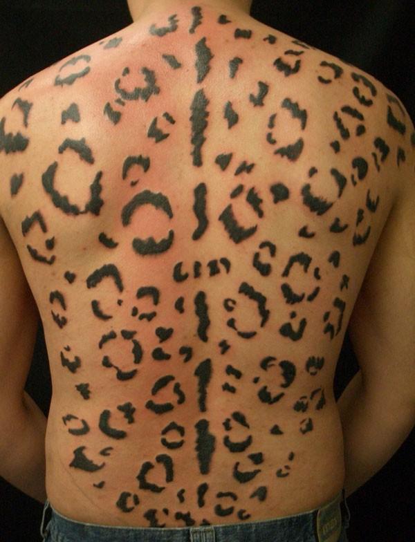 Large black-ink cheetah print tattoo on back