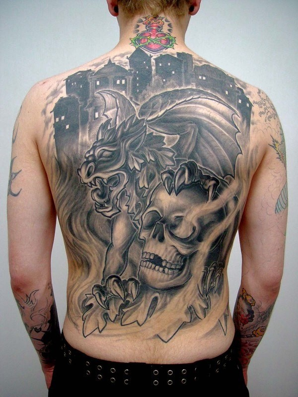 Modern style black ink whole back tattoo of gargoyle combined with human skull in fron of night city