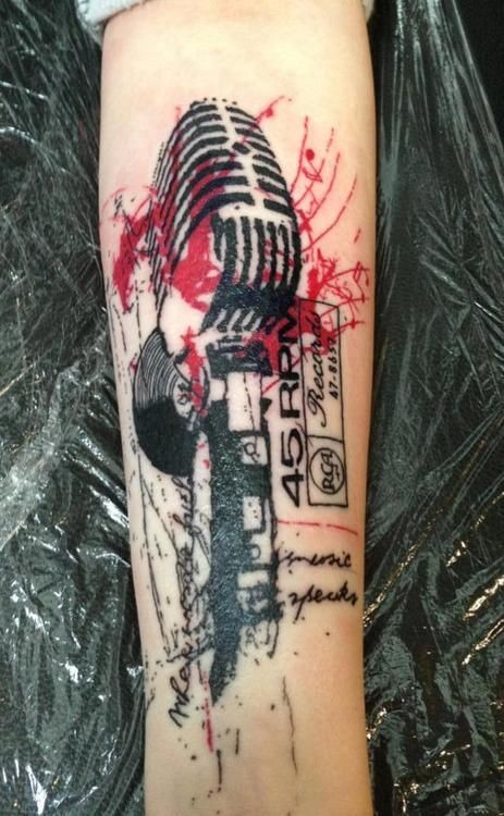 Music themed trash polka arm tattoo of vintage microphone with lettering