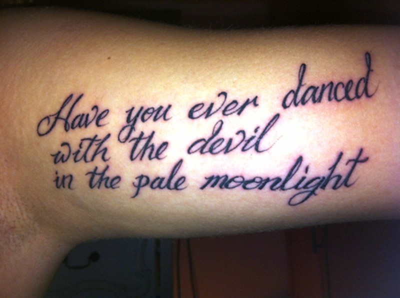 Mystical black-lettered quote tattoo on arm