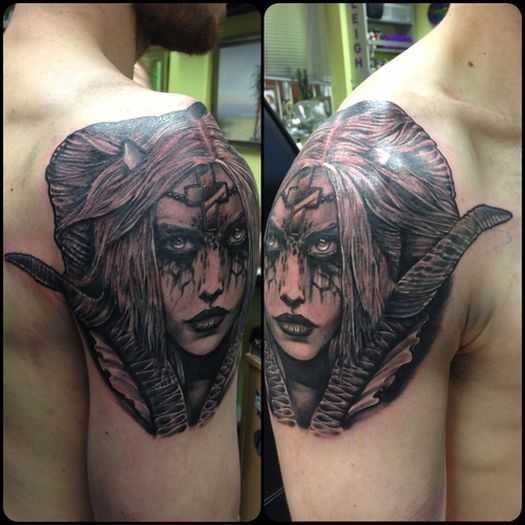 Old looking detailed upper arm tattoo of woman monster with cross