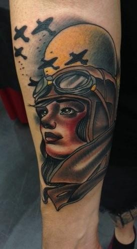 Old school style colroed forearm tattoo of woman pilot combined with planes and moon