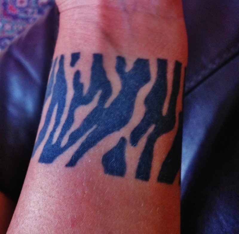 Simple black-ink zebra print band tattoo on wrist