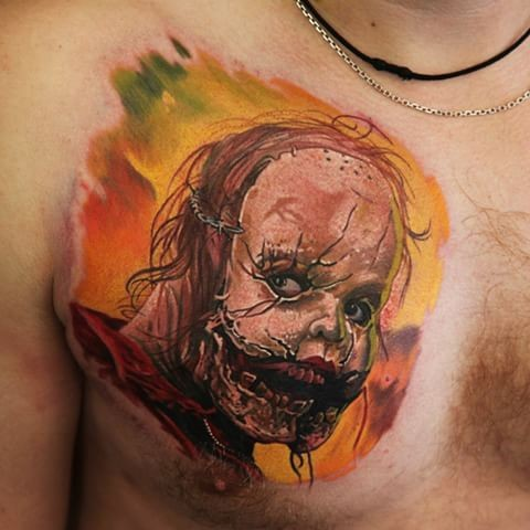 Small funny looking horror monster face tattoo on chest