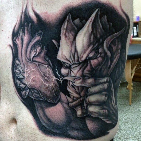Superiror 3D like detailed belly tattoo of gargoyle with human heart