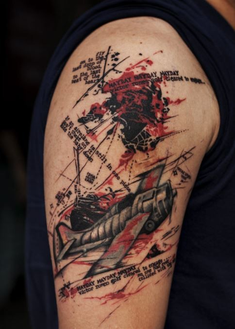 Typical trash polka style upper arm tattoo of old plane with lettering