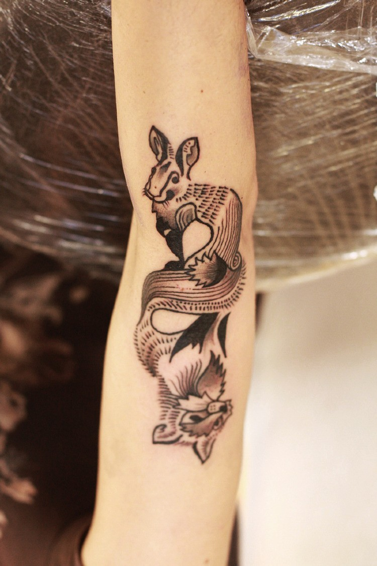 Unusual reflected black-and-white hare and fox tattoo on arm