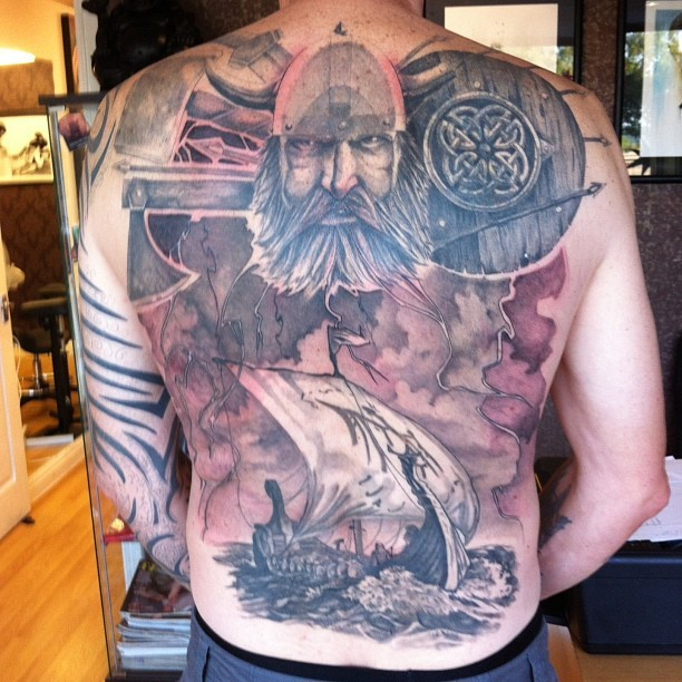 Viking head and ship tattoo on back