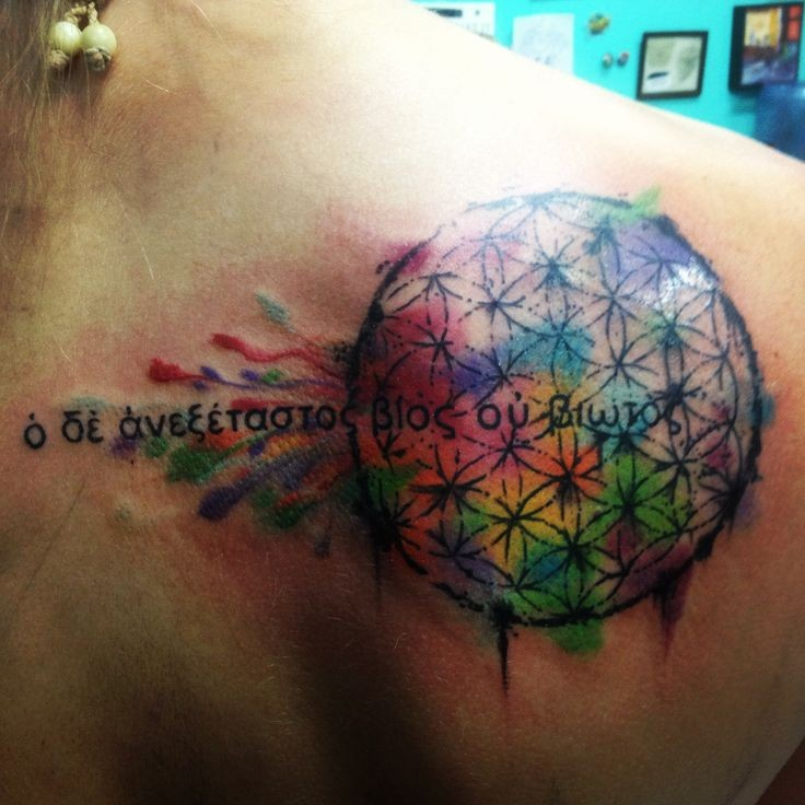 Vivid-colored flower of life with blashes and quote tattoo on back