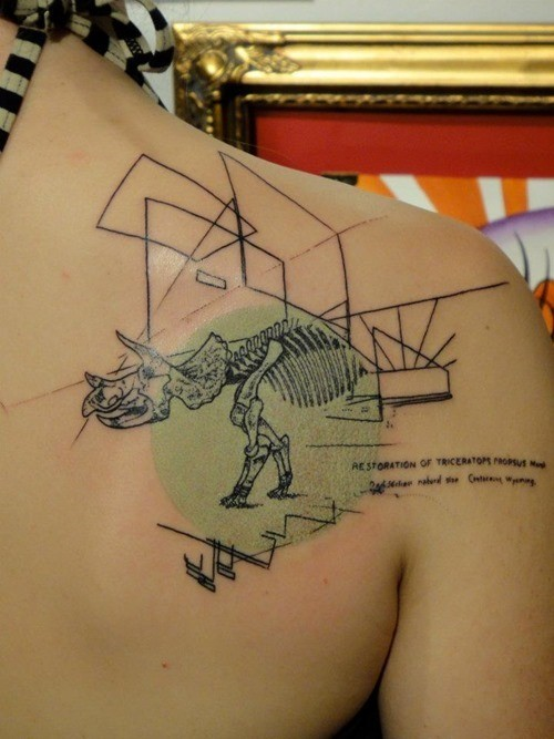 Abstract style colored scapular tattoo of dinosaur skeleton with geometrical figures and lettering