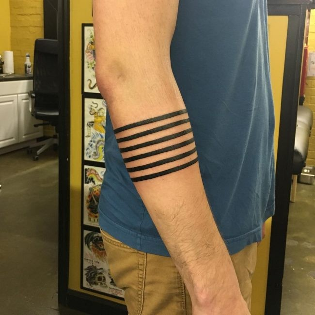 Accurate black ink arm tattoo of parallel lines
