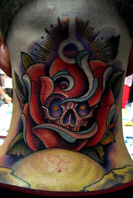 Amazing colored neck tattoo of rose with human skull