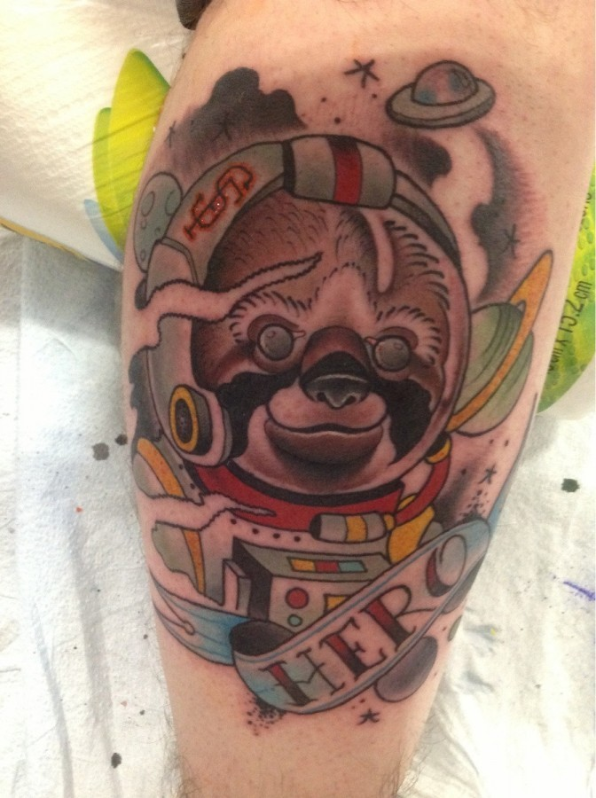 Amazing painted and colored little spaceman sloth with lettering tattoo on arm