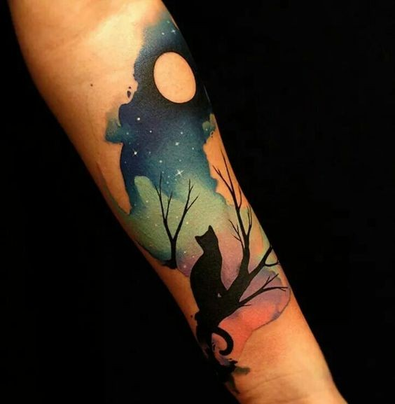 Art style colored forearm tattoo of cat on tree with moon
