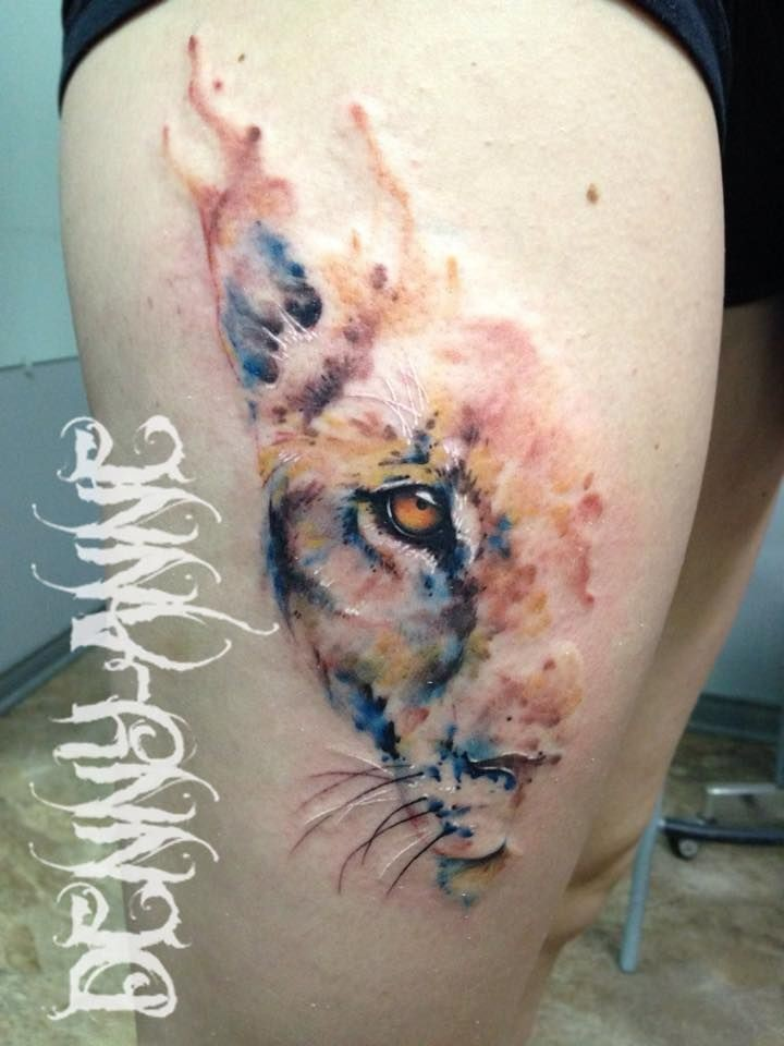 Art style colored thigh tattoo of lion head half