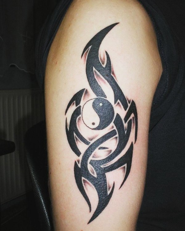 Asian Yin Yang special symbol with dark black tribal style elements tattoo on shoulder