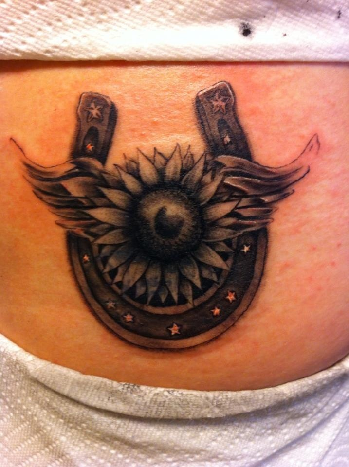 Beautiful horseshoe with flower tattoo on stomach