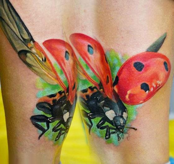 Beautiful vivid colors flying ladybug tattoo