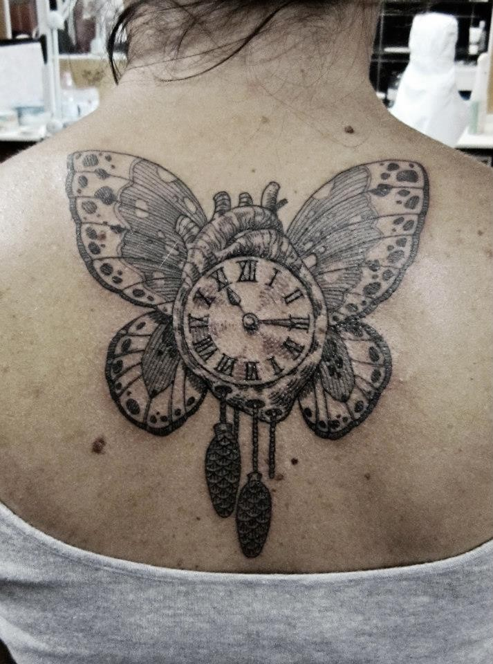 Big amazing looking upper back tattoo of butterfly wings with human heart and clock