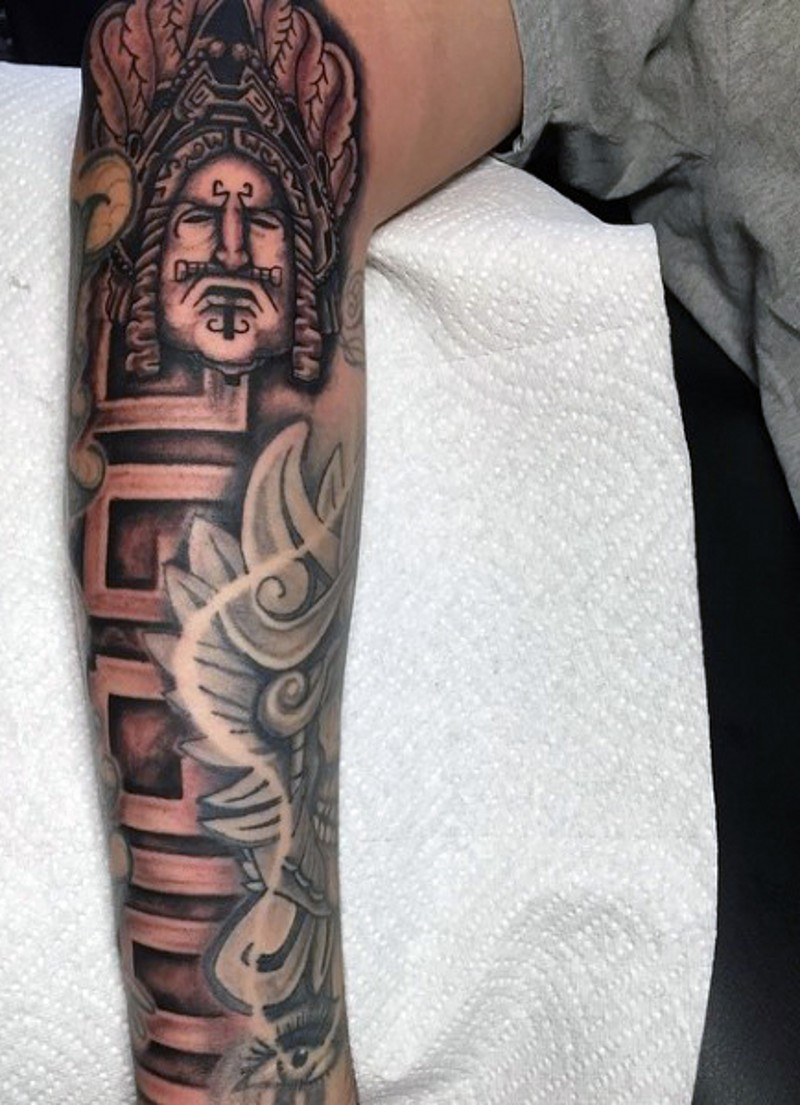 Big half sleeve tribal themed tattoo combined with ambigram