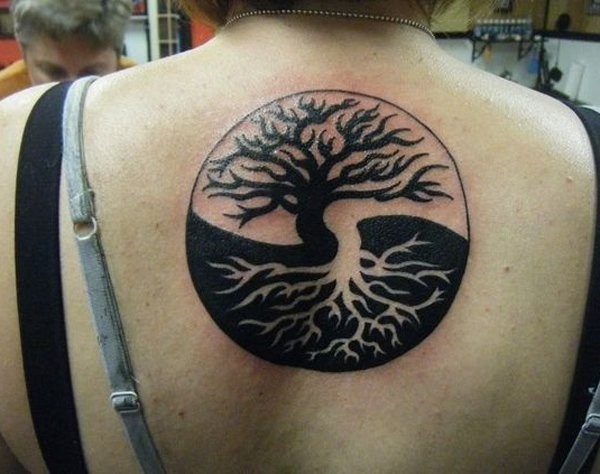 Big size black and white Asian Yin Yang symbol stylized with trees tattoo on upper back
