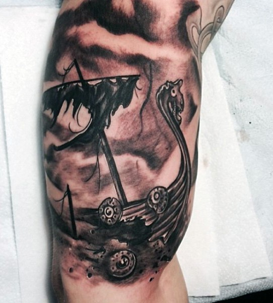Black and gray style biceps tattoo of corrupted viking ship