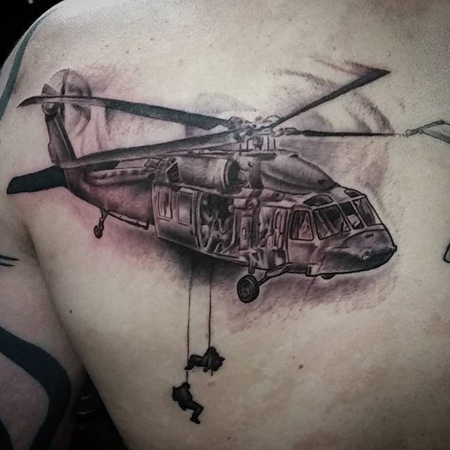 Black and gray style big detailed military helicopter with soldiers tattoo on scapular