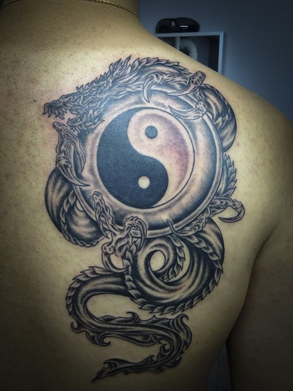 Black and gray style colored shoulder tattoo of Yin Yang symbol with dragon