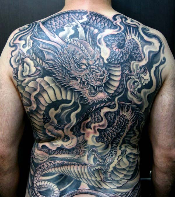 Black and gray style detailed whole back tattoo of creepy dragon with smoke